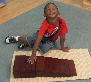 Montessori student with size blocks